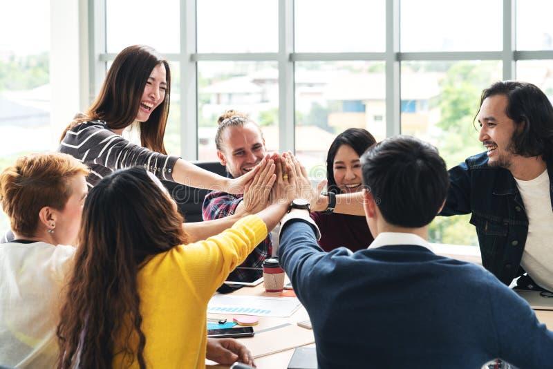 小组年轻不同种族的不同的人民打手势手高五,一起笑和微笑在突发的灵感会议在办公室 图库摄影
