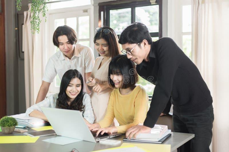 小组年轻亚洲学生高中运作的报告一起在图书馆里 图库摄影