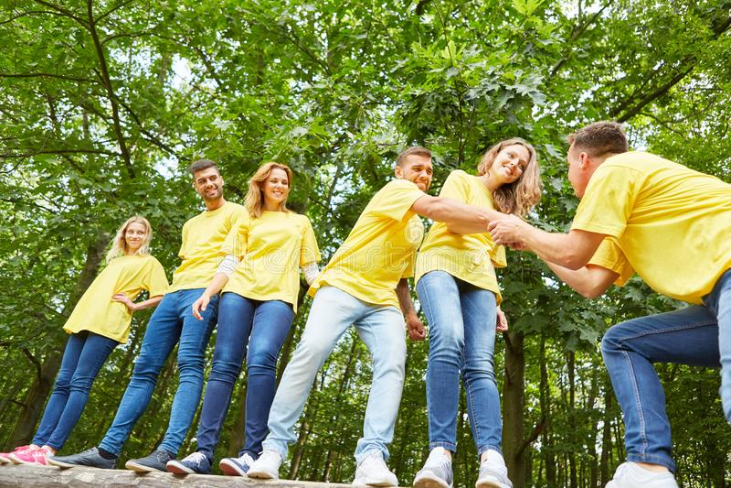小组年轻人在配合互相帮助 库存图片