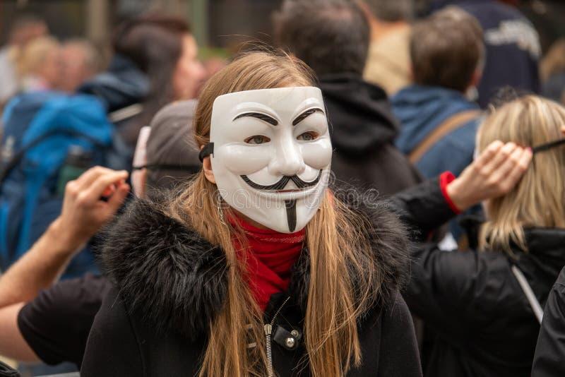 小组年轻人打扮所有在黑色在街道上出去展示与匿名面具 免版税库存照片