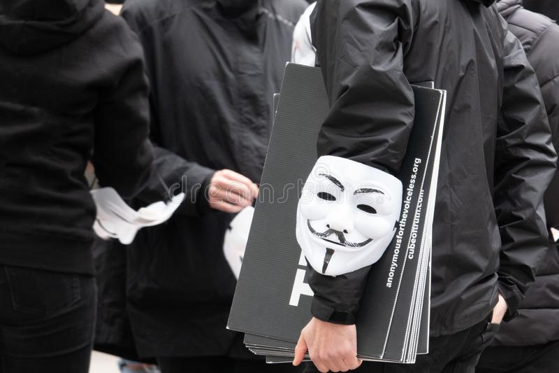小组年轻人打扮所有在黑色在街道上出去展示与匿名面具 免版税库存图片