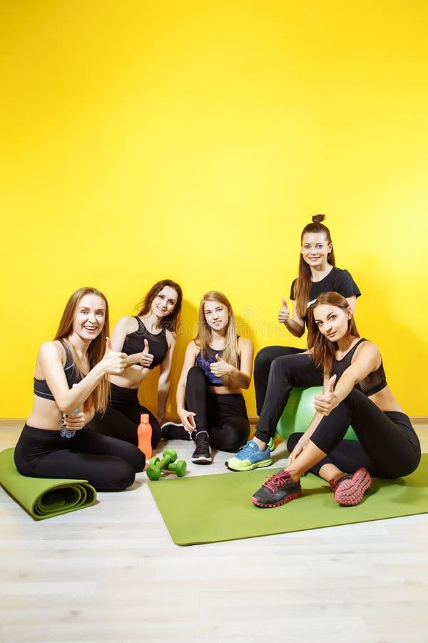 小组年轻人炫耀显示在黄色背景的妇女赞许 库存图片
