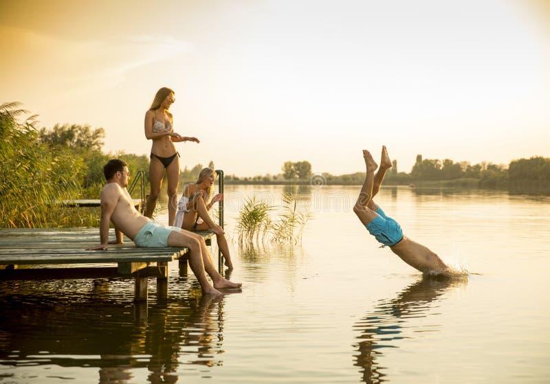 小组年轻人获得在码头的乐趣在湖 库存照片