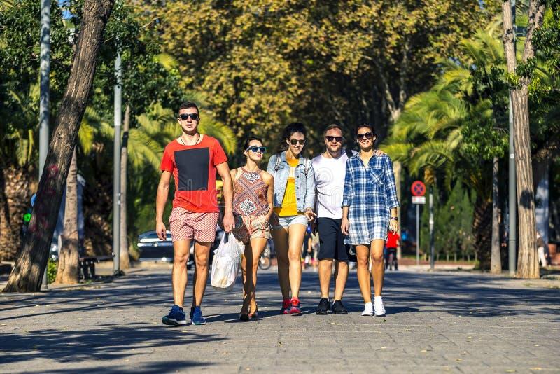 小组年轻和可爱的人民沿胡同去 免版税库存照片