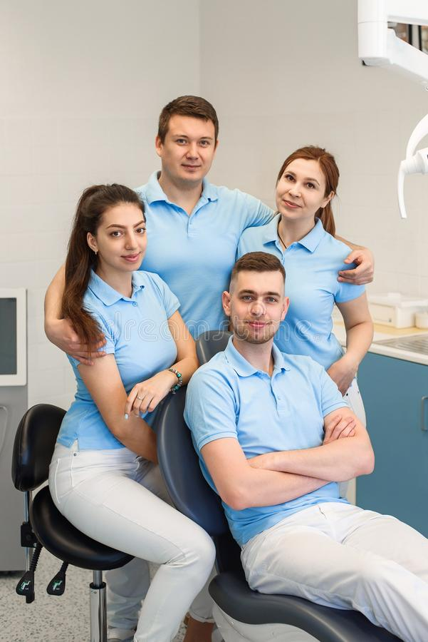 小组年轻和愉快的牙齿医生站立靠近彼此在牙齿诊所 配合和企业概念 库存图片