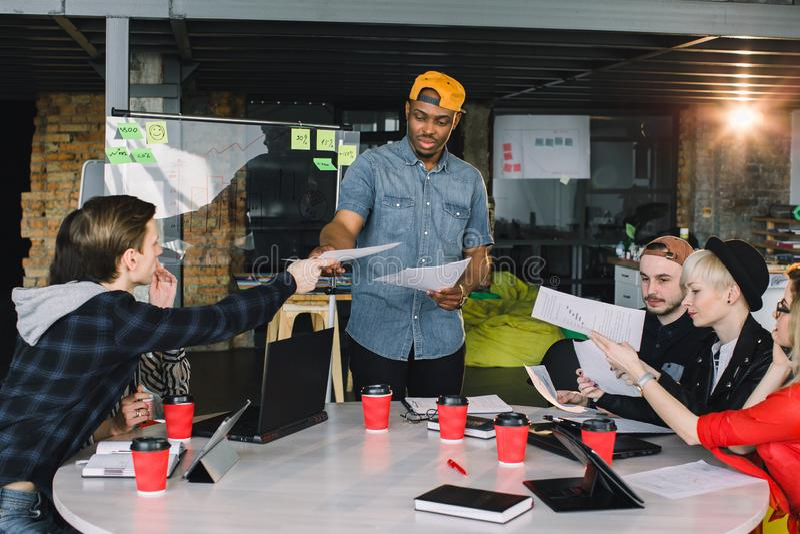 小组年轻商人会集了一起谈论创造性的想法 坐在桌上的小组国际学生 免版税库存图片