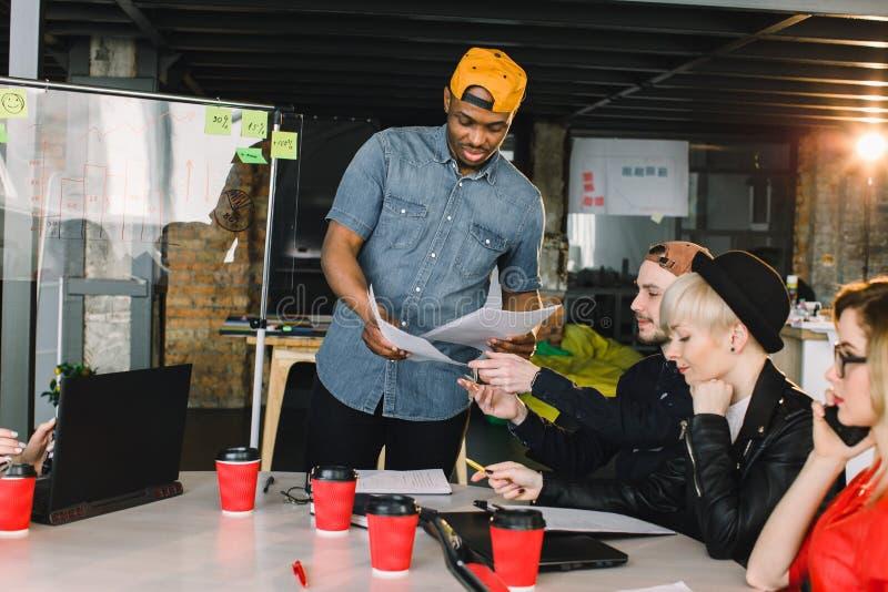 小组年轻商人会集了一起谈论创造性的想法 坐在桌上的小组国际学生 免版税库存照片