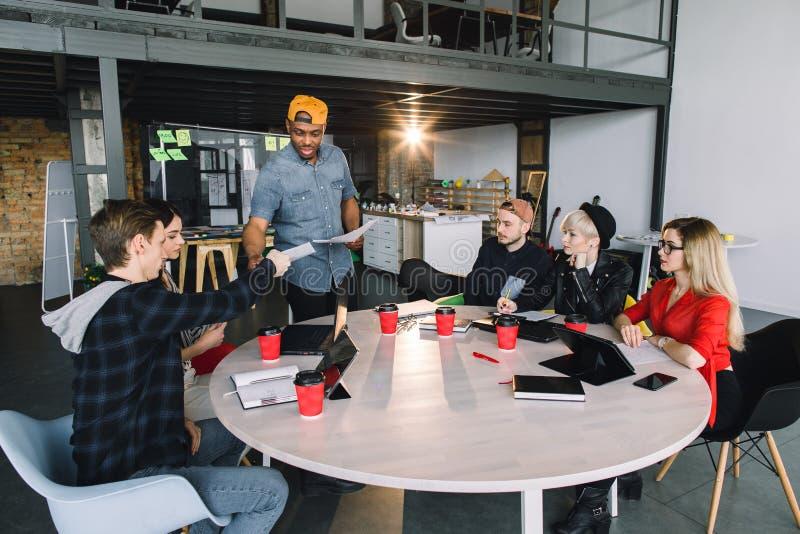 小组年轻商人会集了一起谈论创造性的想法 坐在桌上的小组国际学生 库存图片