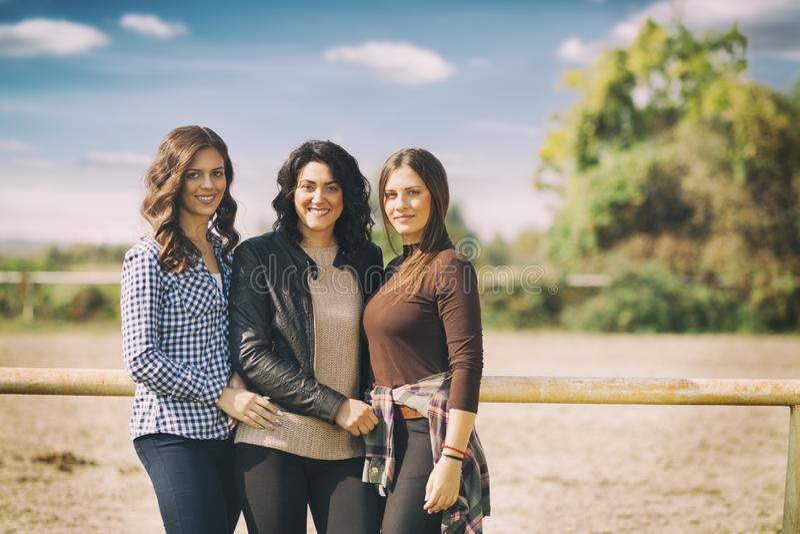 小组年轻女人,三个朋友在coutryside和笑享用在一个夏日,享受假期 免版税库存照片