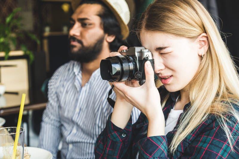 小组年轻快乐的朋友在咖啡馆坐,吃,喝饮料 朋友采取selfies并且拍照片 库存照片