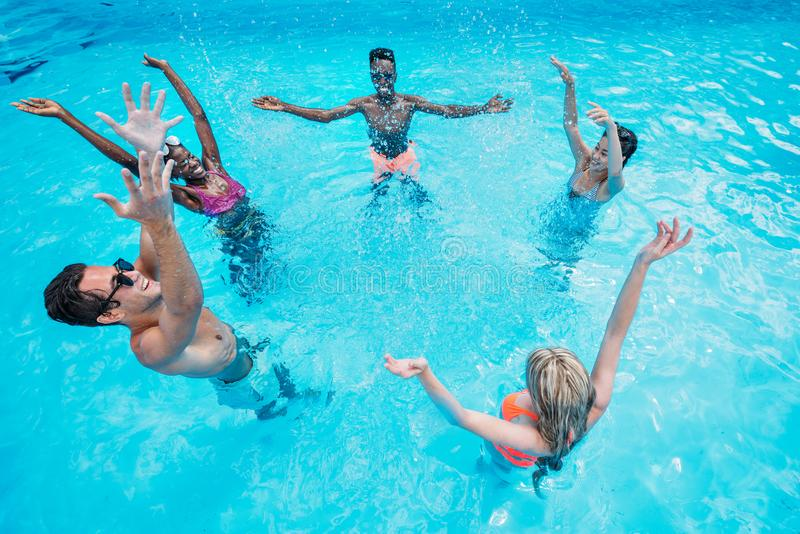 小组年轻愉快的不同种族的人民获得乐趣一起在游泳 库存图片