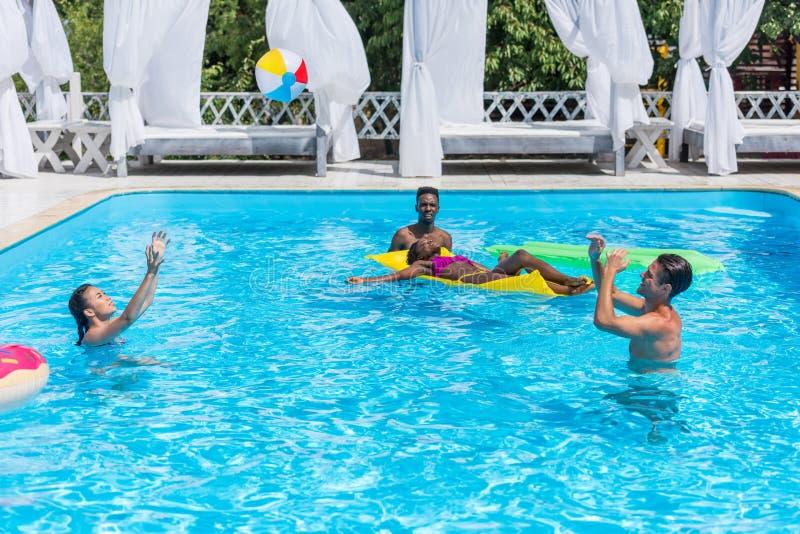 小组年轻愉快的不同种族的人民获得乐趣一起在游泳 免版税库存照片
