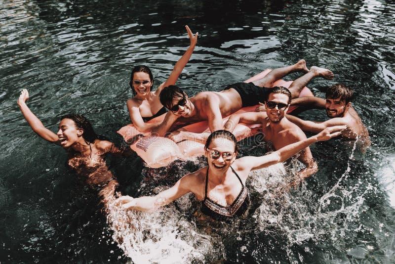 小组年轻愉快的人民获得乐趣在水池 库存照片