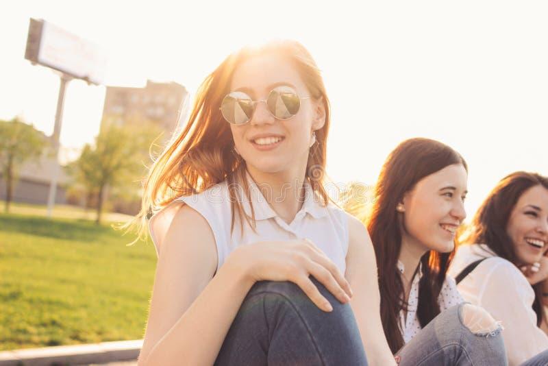 小组年轻愉快的女朋友享有在夏天城市街道,日落背景上的生活 图库摄影
