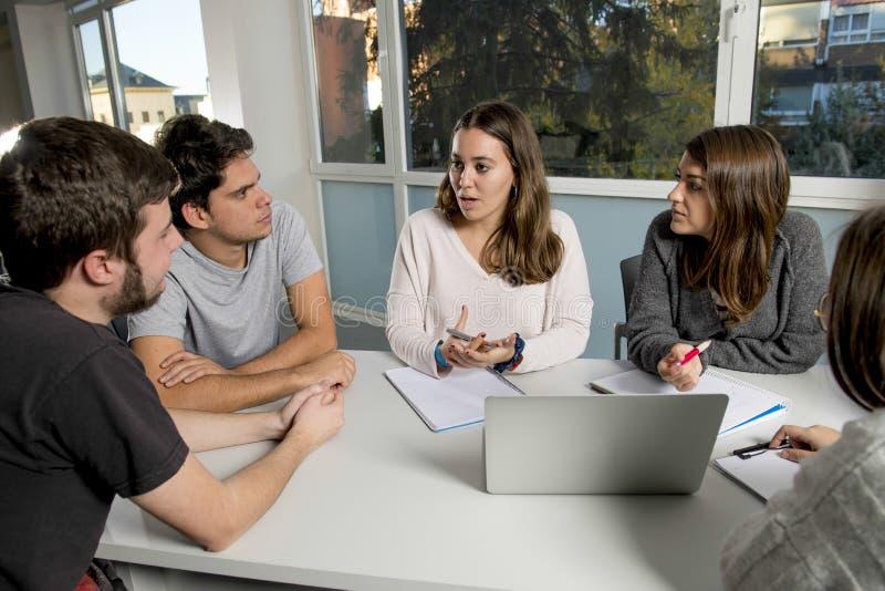小组年轻男性和女性少年在学校坐教室学会和工作在项目togethe的大学生 免版税库存图片