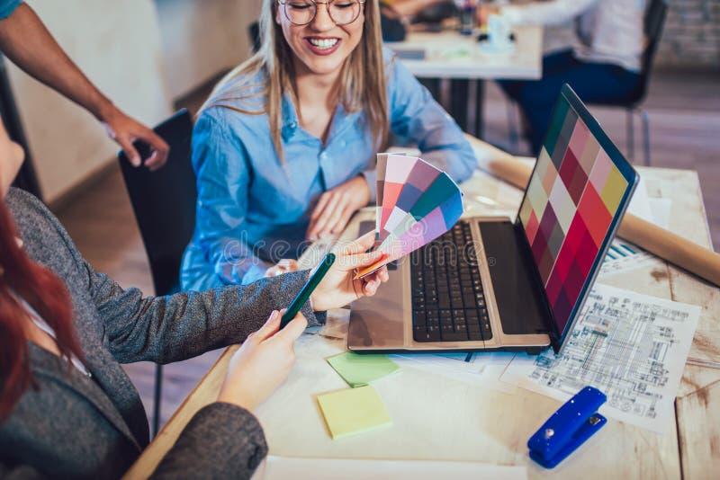 小组年轻看色板显示的商人和设计师 免版税图库摄影