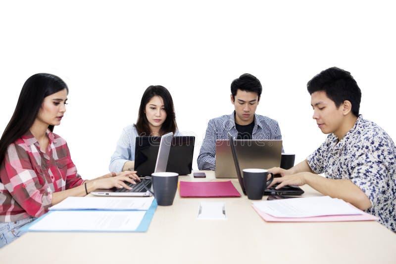 小组年轻自由职业者看起来繁忙在演播室 免版税库存图片