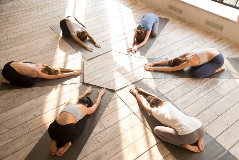 小组年轻运动的人民实践的瑜伽教训,Balasana po 免版税库存图片