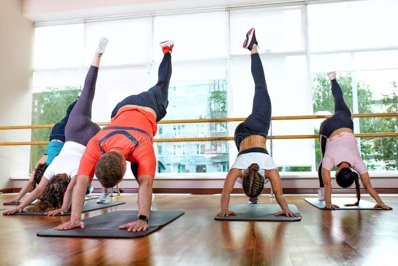 小组年轻运动的可爱的与辅导员的人民实践的瑜伽教训,一起站立在锻炼,运作 库存照片