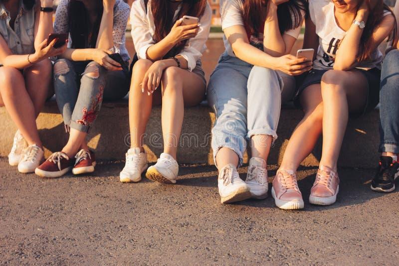 小组庄稼照片使用在日落背景的年轻愉快的棕褐色的女孩朋友机动性 库存图片