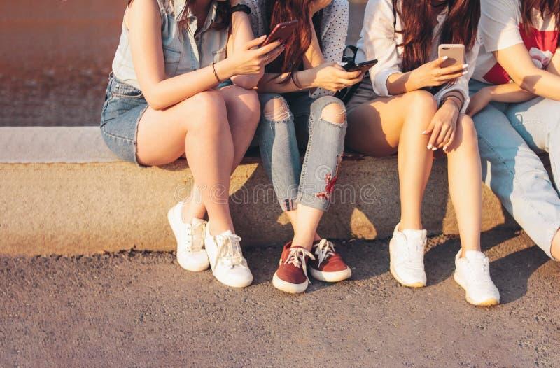 小组庄稼照片使用机动性的年轻愉快的女孩朋友学生在日落背景的城市街道 库存图片