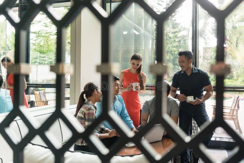 小组快乐的雇员在休息室区域的喝咖啡 库存图片