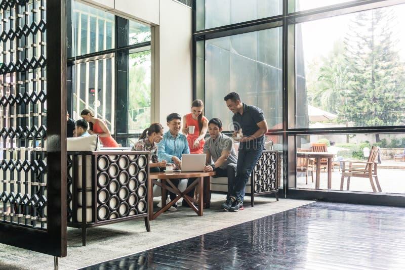 小组快乐的雇员在休息室区域的喝咖啡 免版税库存照片