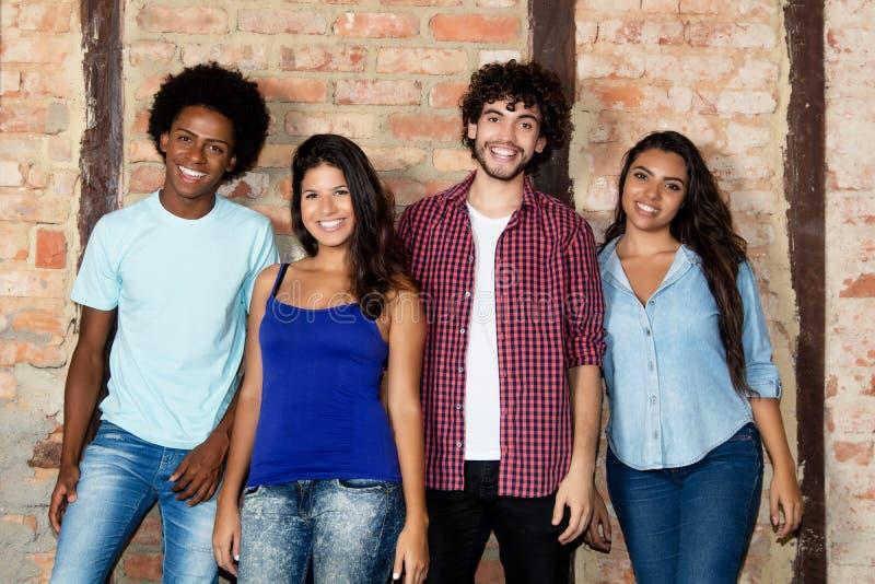 小组愉快不同种族年轻人和妇女室内看 图库摄影