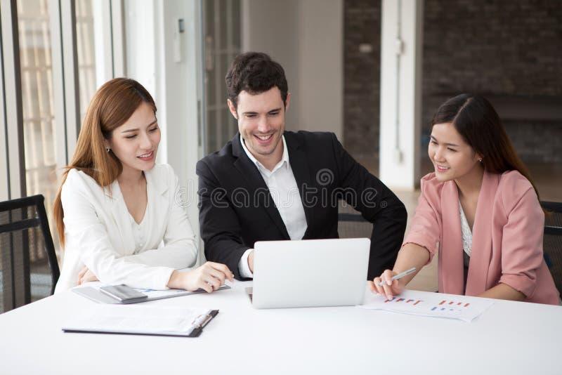 小组愉快的一起研究膝上型计算机的商人男人和妇女在候选会议地点 两个女孩亚洲人和白种人配合  免版税图库摄影