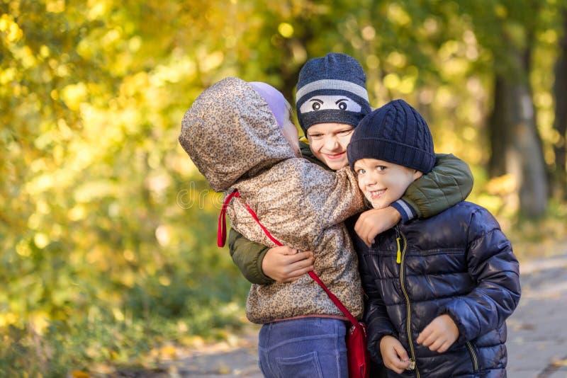小组愉快的三个孩子获得乐趣户外在秋天公园 逗人喜爱的孩子喜欢一起拥抱反对金黄秋天背景 免版税库存照片