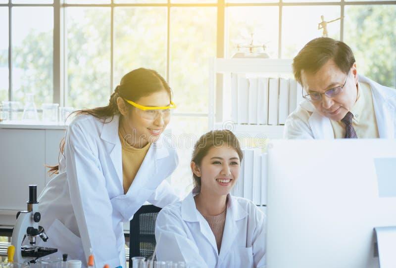 小组愉快的与资深教授的变化医科学生研究新的项目一起在实验室 免版税库存图片