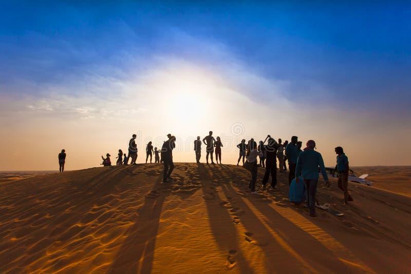 小组愉快的人剪影在沙漠 免版税库存图片