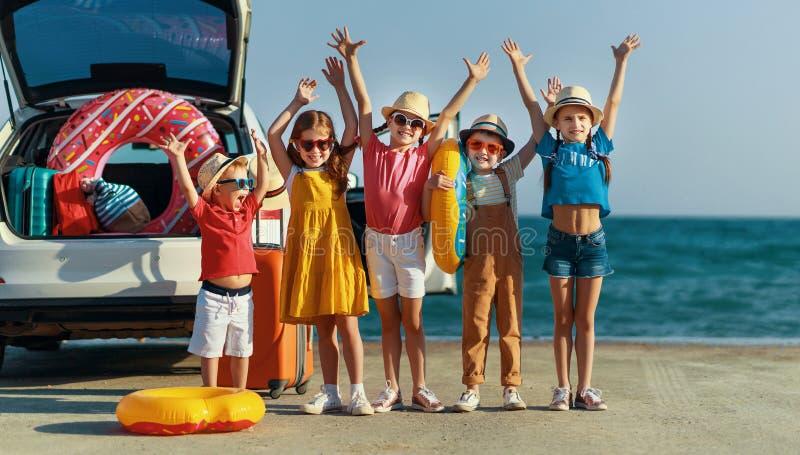 小组愉快的儿童女孩和男朋友汽车乘驾的对夏天旅行 免版税库存照片