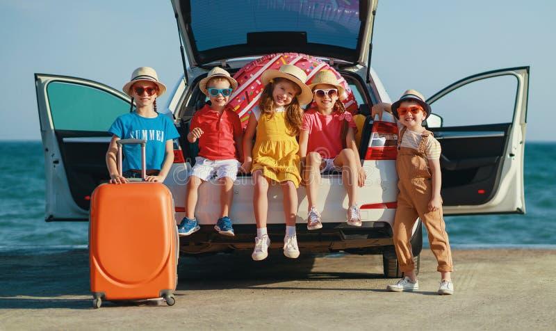 小组愉快的儿童女孩和男朋友汽车乘驾的对夏天旅行 免版税库存图片