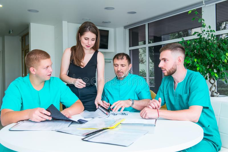 小组愉快的医生或实习生有辅导者会议的和采取笔记在医院 医疗教育,医疗保健,人们和 免版税库存照片