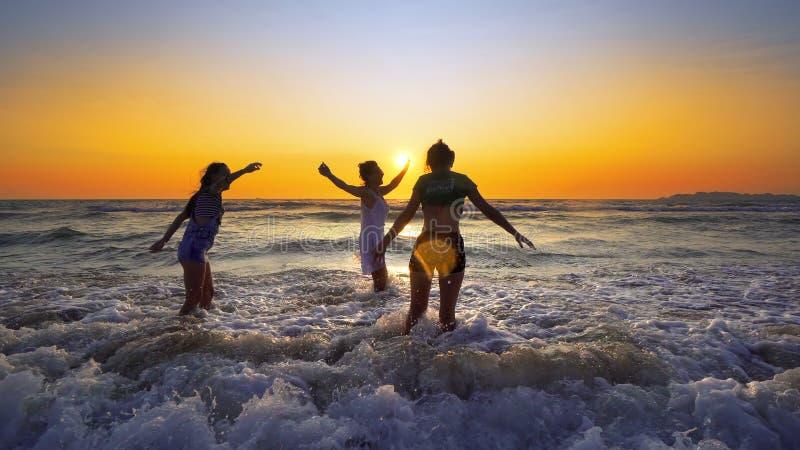 小组愉快的女孩跳过海波浪在日落的海滩 免版税库存图片