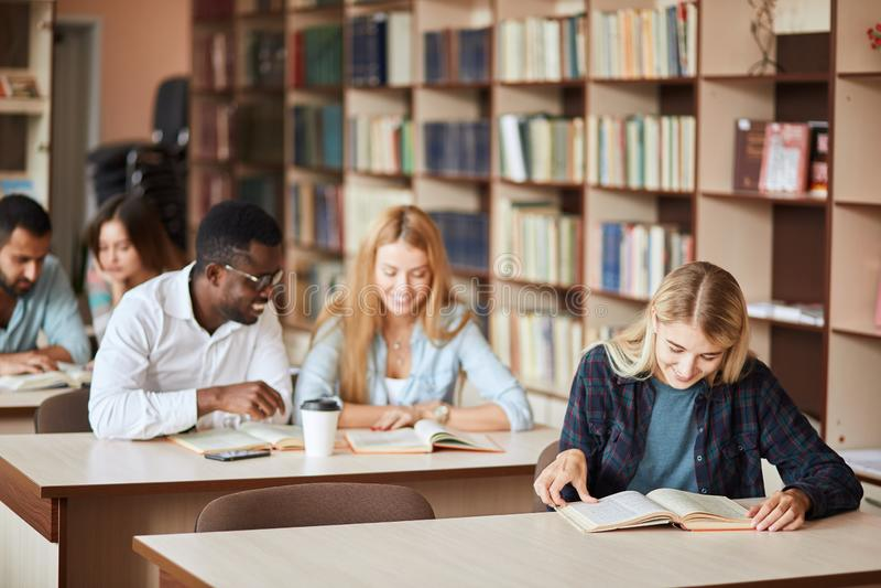 小组愉快的学生看书和准备对检查在图书馆里 图库摄影