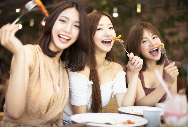 小组愉快的朋友吃晚餐在餐馆 免版税库存图片