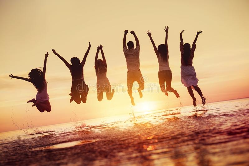 小组愉快的朋友在日落水中跳 免版税图库摄影