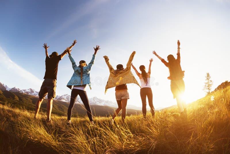 小组愉快的朋友山日落被举的胳膊 图库摄影
