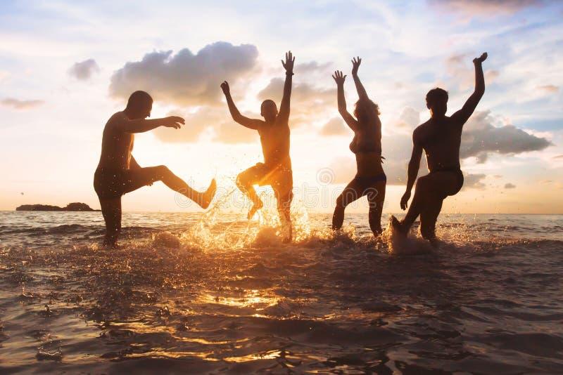 小组愉快的朋友或家庭获得乐趣一起在海滩在日落,跳跃和跳舞 库存照片