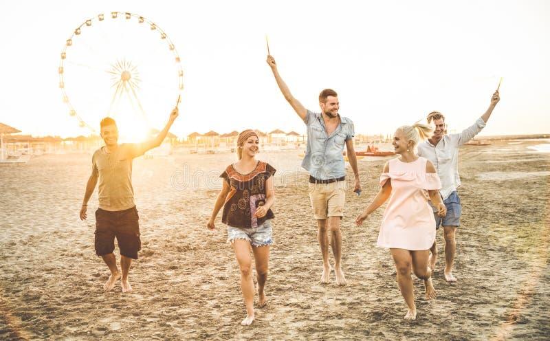 小组愉快的朋友获得在海滩的乐趣在日落 库存图片