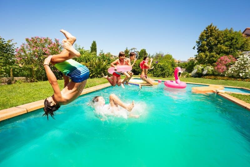小组愉快的青少年获得乐趣在游泳场 库存图片