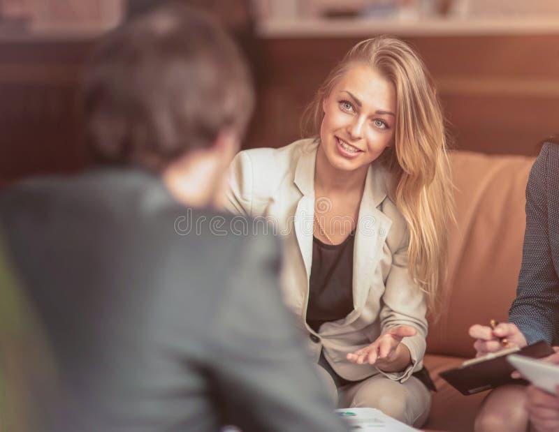 小组成功的商人 关于重要交易的讨论在有商务伙伴的办公室 图库摄影