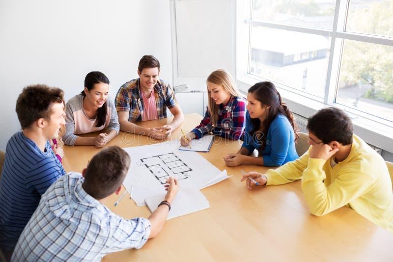 小组有图纸的微笑的学生 免版税库存图片