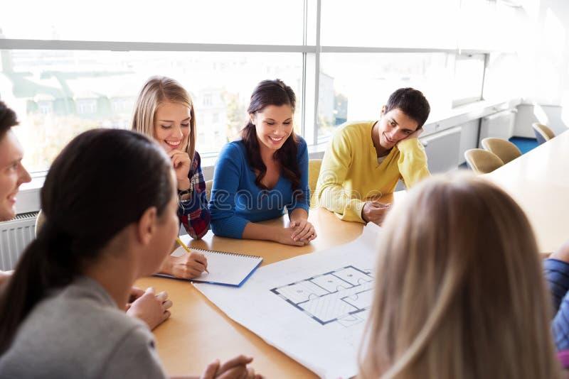 小组有图纸的微笑的学生 免版税库存照片