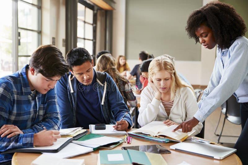 小组有工作在书桌的女老师的高中学生 免版税库存照片