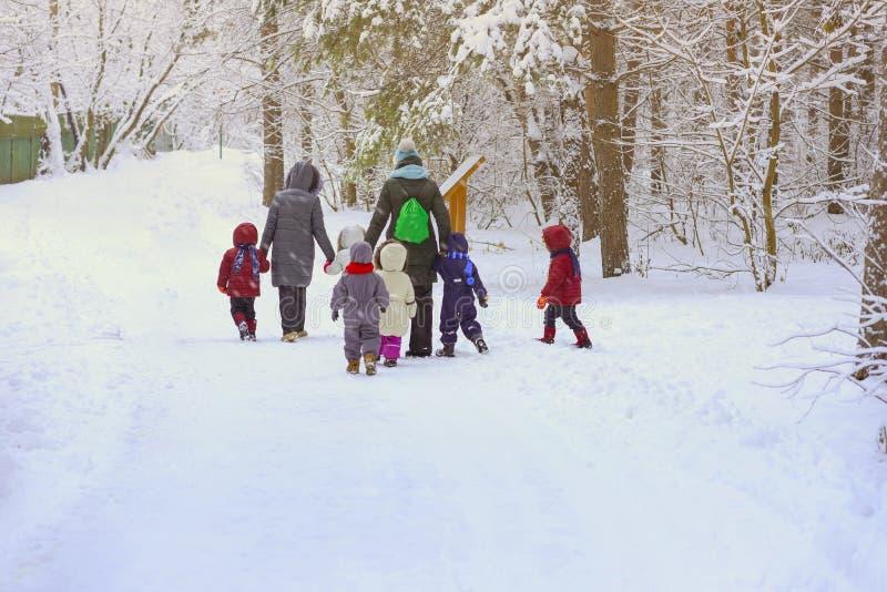小组有幼儿园的老师的无法认出的小孩,回到我们,握手在多雪的公园,冬天的步行 图库摄影