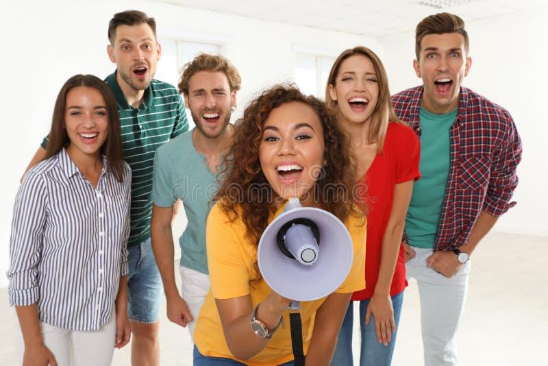 小组有扩音机的愉快的青年人 库存图片