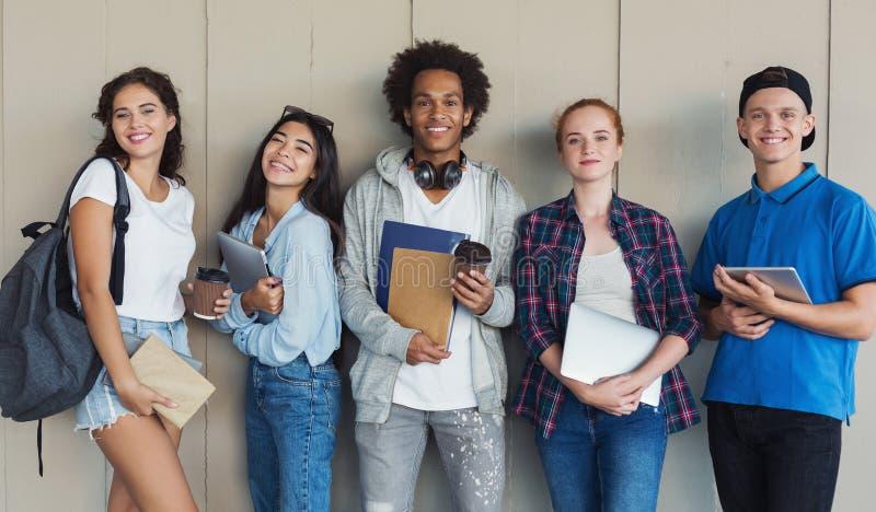 小组有文件夹和书包的种族少年学生 库存图片